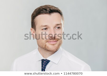 Close up portrait of handsome young man with stubble, looks pensively aside, thinks about something, Stock photo © vkstudio