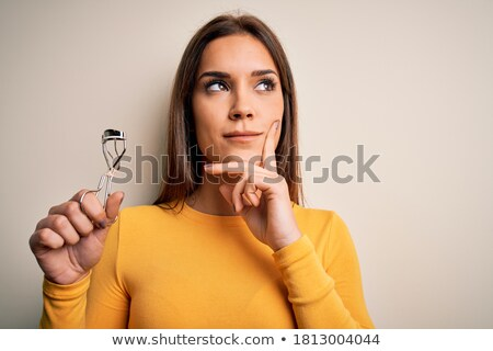 Confused young woman holding eyelash curler. Stock photo © deandrobot