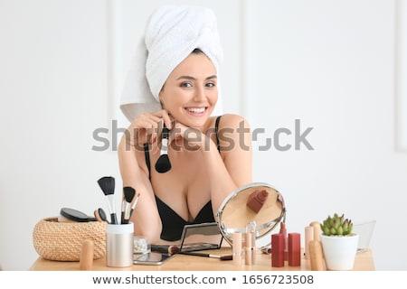beautiful young woman applying makeup stock photo © dotshock