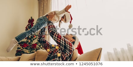 Young happy family near a Christmas tree at home holding gift an stock photo © HASLOO