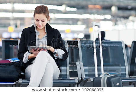Young female passenger at the airport, using her tablet computer stock photo © lightpoet