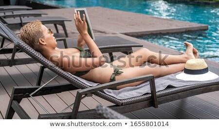 Seductive bikini woman relaxing on a deckchair stock photo © stockyimages