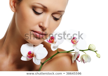 smiling woman with orchid flower on her shoulder stock photo © dolgachov