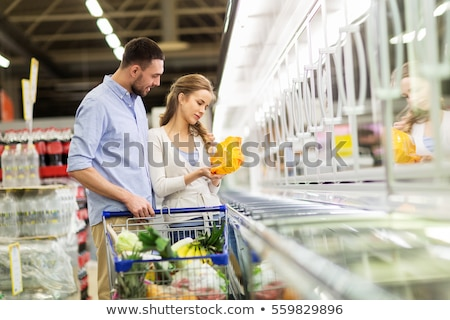young man shopping for frozen food in a grocery store stock photo © hasloo
