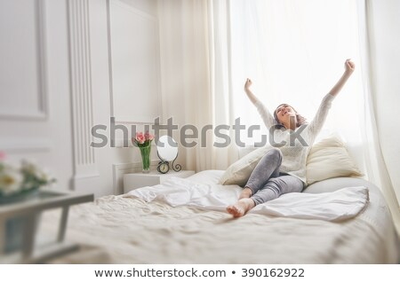 Young woman enjoying a lazy day in bed Stock photo © dash