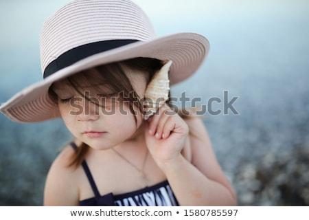 Girl in hat listening seashell stock photo © Agatalina