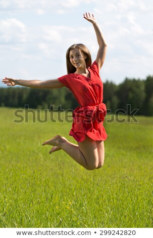 Young girl in a red dress jumping in a field coniferous forest Stock photo © RuslanOmega