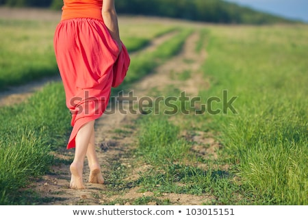 Stock photo: Barefoot woman walking in a green field