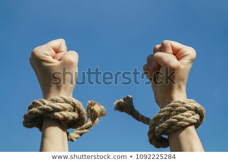 Hands with clenched fists in shackles - slavery concept Stock photo © gomixer