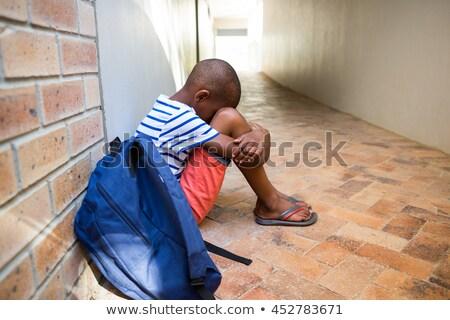 Smutne chłopca posiedzenia ściany korytarz Zdjęcia stock © wavebreak_media