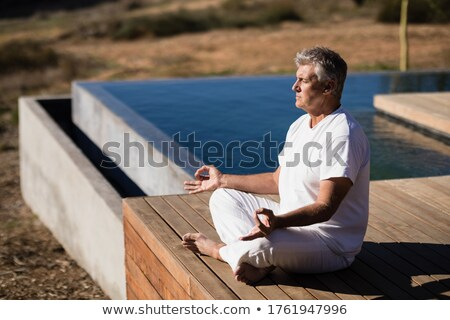 Man practicing yoga on wooden plank Stock photo © wavebreak_media