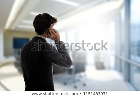 businessman standing next to office window and using smartphone stock photo © stevanovicigor