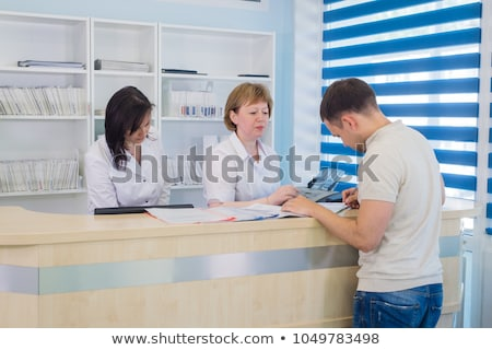 a nurse sitting at a computer at the reception area of a hospita stock photo © monkey_business