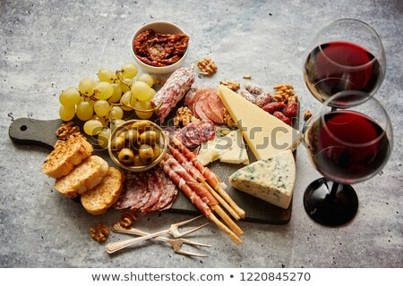 Cold snacks board with meats, grapes, wine, various kinds of cheese Stock photo © dash