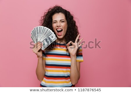 image of joyous woman 20s with curly hair holding fan of dollar stock photo © deandrobot