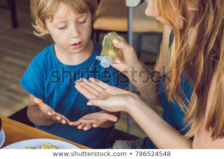 Mother and son using wash hand sanitizer gel in the cafe Stock photo © galitskaya