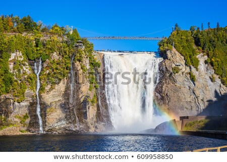 blue lake and powerful waterfall montmorency in montmorency falls park in quebec stock photo © lopolo