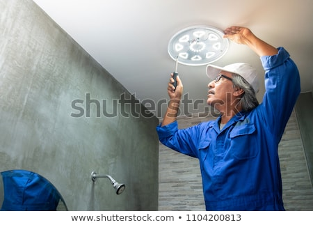 Man Technician servicing at work on electric room Stock photo © Lopolo