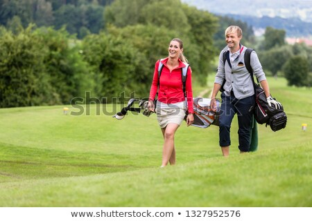 smiling golf players carrying their club bags stock photo © kzenon