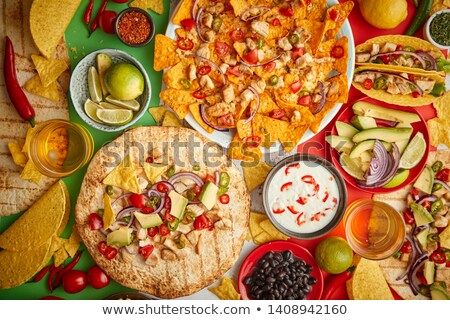 an overhead photo of an assortment of many different mexican foods on a table stock photo © dash