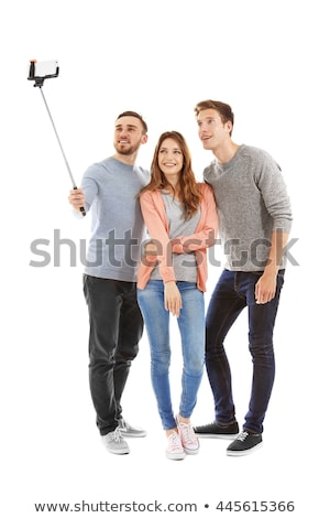 friends take picture by smartphone on selfie stick stock photo © dolgachov