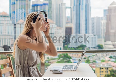 Young woman teaches a foreign language or learns a foreign language on the Internet on her balcony a Stock photo © galitskaya