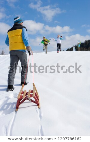 Father And Son Pulling Sledge Up Snowy Hill Stock photo © monkey_business