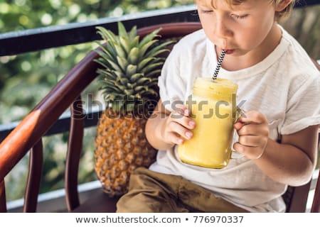 A boy drinks a pineapple smoothie on the terrace Stock photo © galitskaya