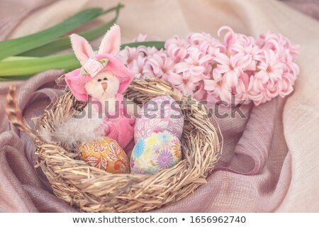 easter eggs in straw nest and chocolate bunnies stock photo © dolgachov