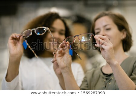 Hands of young consultant and her client comparing two models of eyeglasses Stock photo © pressmaster