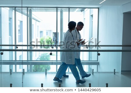 Side view of matured Caucasian male physician interacting and showing papers to senior Caucasian cou Stock photo © wavebreak_media