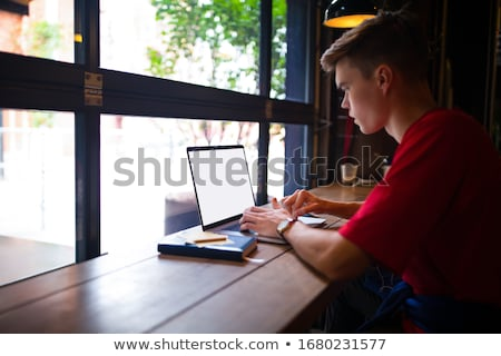 Fashionable male student types publication on laptop computer, prepares for exam, spends time on edu Stock photo © vkstudio