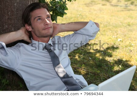 Young exec using a laptop under a tree Stock photo © photography33