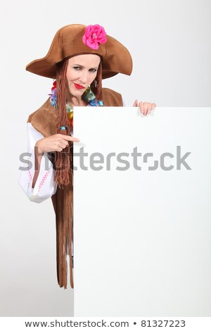 Woman in a seventies hippy costume pointing at a board left blank for your message Stock photo © photography33