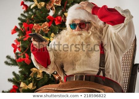 Święty mikołaj posiedzenia wygodny bujane choinka domu Zdjęcia stock © HASLOO