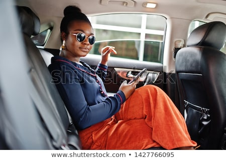 Businesswoman sitting in car and calling by phone Stock photo © HASLOO