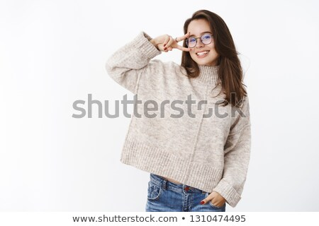 Grinning woman in sweater near wall looking over Stock photo © dash