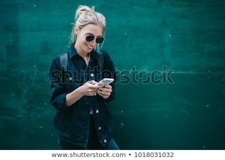 Happy young woman sending a text message Stock photo © dash
