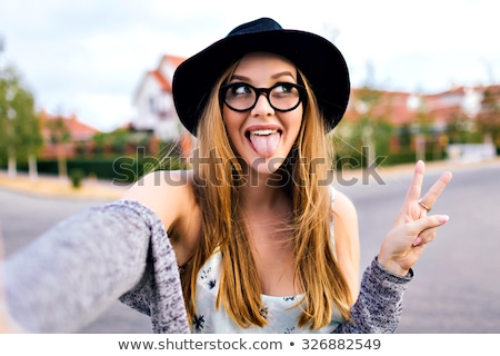 funny girl in glasses making funny face and taking selfie stock photo © deandrobot
