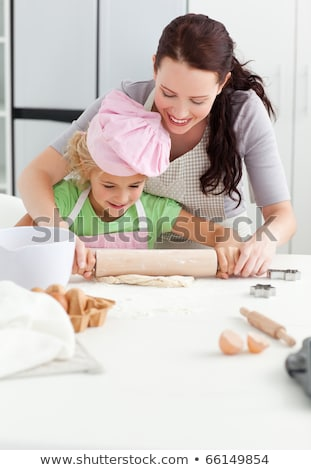 Mother and daughter rolling dough with rolling pin in kitchen Stock photo © wavebreak_media
