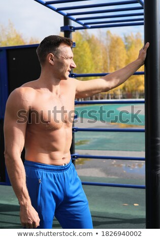 sports man standing at the stadium outdoors and looking aside stock photo © deandrobot