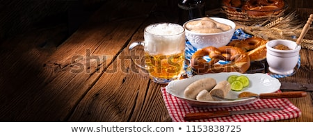 Oktoberfest. Mug of beer and Sausage on a background of blue rho Stock photo © popaukropa