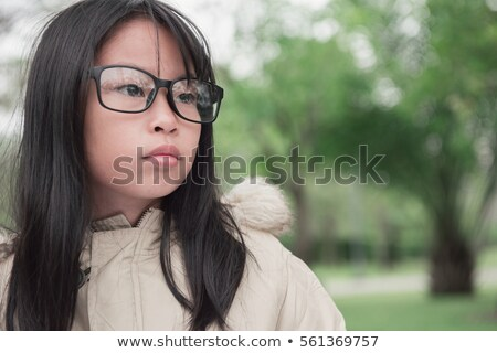 Cute Asian Chinese girl with glasses in park Stock photo © kenishirotie
