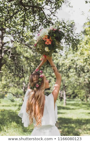 back view of bride in white dress throwing wedding bouquet, isolated on white stock photo © LightFieldStudios