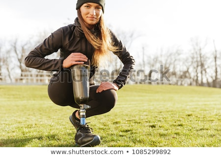 Image of young handicapped sportswoman in tracksuit, squatting a Stock photo © deandrobot