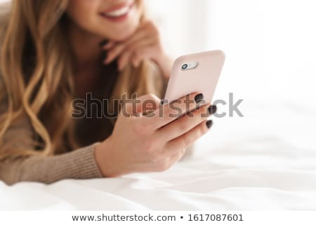 cropped image of a satisfied woman using mobile phone stock photo © deandrobot