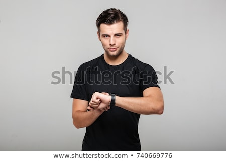 Smiling young casual man adjusting his smart watch Stock photo © deandrobot