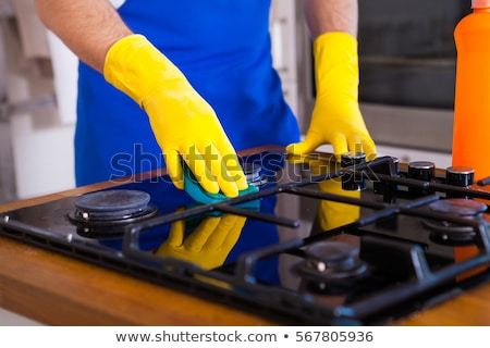 man with spray cleaning cooker at home kitchen Stock photo © dolgachov