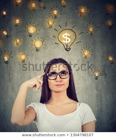 woman looking up at dollar idea light bulbs above head deciding how to earn morney stock photo © ichiosea