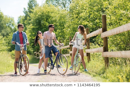 Stock photo: happy friends with fixed gear bicycles in summer